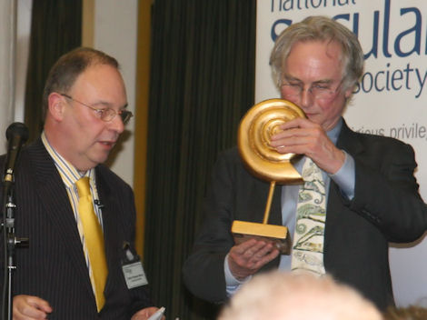Richard Dawkins inspects a 'golden ammonite' trophy before presenting it